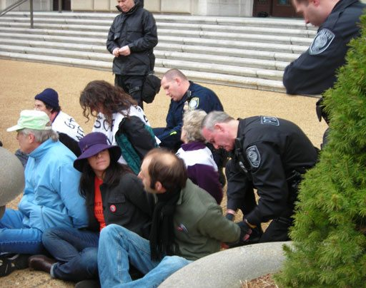 Police handcuff six of the dozens of protesters arrested outside the IRS building.(Kristi King/WTOP Photo)