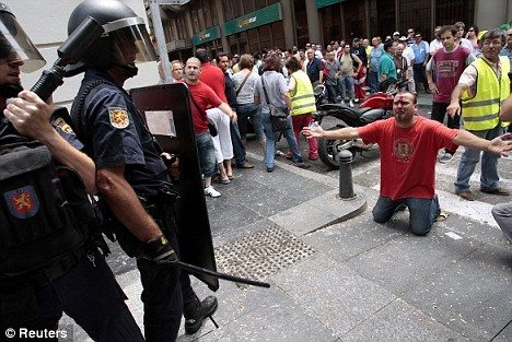 An injured farmer kneels in front of riot police during clashes between fuel-protest farmers and riot police in Almeria