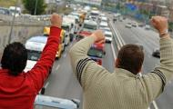 Two men give their support to Spanish truckers blocking the roadway into Madrid