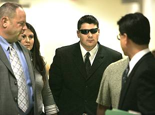 SDPD officer Frank White (in sunglasses) walks with his wife Jacquellyn and his lawyers to an appearance in Vista Superior Court. White is arraigned on charges including felony gross negligent discharge of a firearm. Photo - Charlie Neuman
