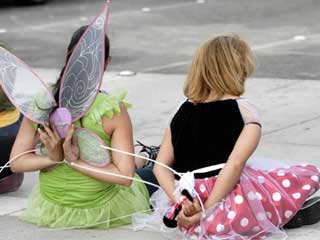 Protesters dressed as Tinker Bell and Snow White sit after being arrested at Disneyland protest.