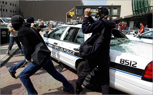 Violence erupted between some protesters and police. At left, protesters smashed a police car. (AP)